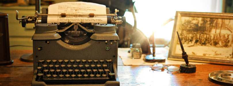 A typewriter, quill pen and framed picture on an old desk.